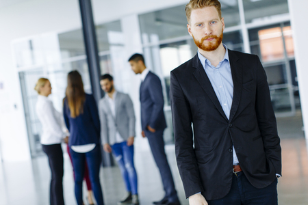 Businessman standing in the office and other business people talking at background Stock Photo