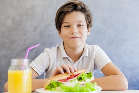 niños desayunando: Portrait of cute teen boy having breakfast at home Foto de archivo