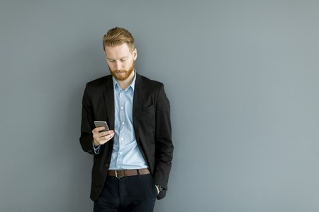 Portrait of redhair man using mobile phone standing by the wall Stock Photo