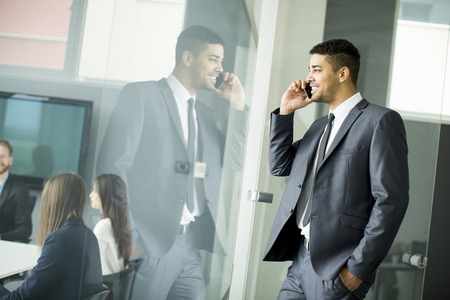 Young african businessman using mobile phone in his modern office. Stock Photo
