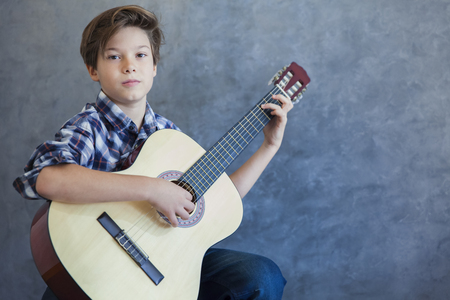 Teen boy with acustic guitar against wall