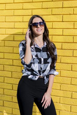 Portret van een elegante vrouw die mobiele telefoon voor een gele muur met behulp van