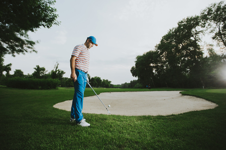 Young man playing golf on a sunny day on a beautiful golf course