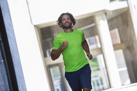 Athletic young man running and working out in urban enviroment Stock Photo