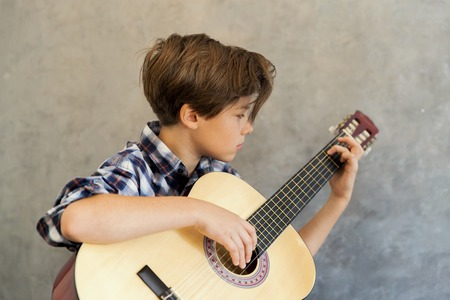 Portrait of Teen boy playing acoustic guitar