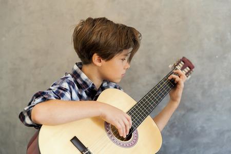 portrait de l & # 39 ; adolescence garçon jouant de la guitare acoustique