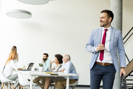 Young businessman leaves a meeting while other business people stay in office Stock Photo