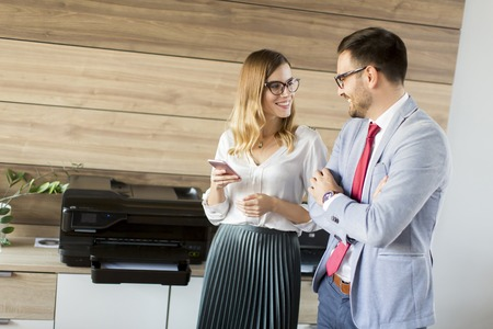 Young business couple talking in office by the scanner mashine