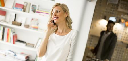 Porträt der Geschäftsfrau stehend gegen Wand und spricht am Handy Standard-Bild - 88567649