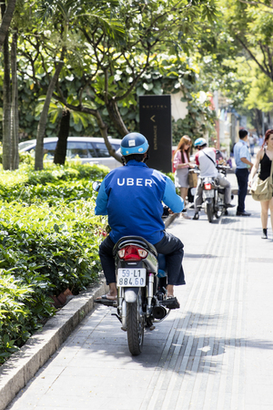 HO CHI MINH, VIETNAM - FEBRUARY 22, 2017: Unidentified Uber driver on motorcycle on street of Ho Chi Minh, Vietnam. Ho Chi Minh is the largest city in Vietnam. Editorial