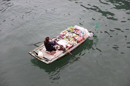 HA LONG, VIETNAM - FEBRUARY 28, 2017: Unidentified woman in boat at Ha Long Bay in Vietnam. Ha Long Bay is a UNESCO World Heritage Site and popular travel destination in Vietnam. Редакционное
