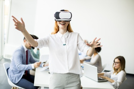 Excited businesswoman in virtual reality glasses trying to touch cyber objects while other business people have meeting