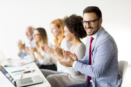 View of multiracial business people around  table during staff meeting and smiling Stock Photo