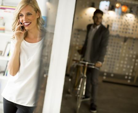 Porträt der Geschäftsfrau stehend gegen Wand und spricht am Handy Standard-Bild - 88608056