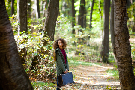 Curly hair teen girl with retro suitcase posing  in autumn forest