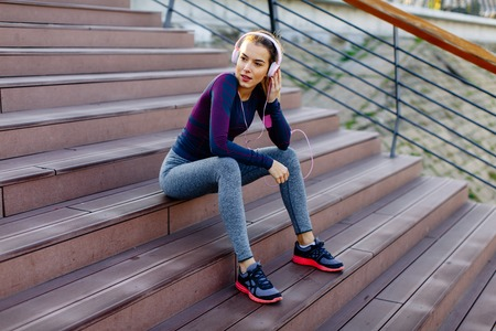 Young attractive female runner taking break after jogging outdoors