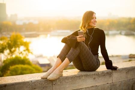 야외에서 스마트 폰에서 유행 젊은 여자 듣는 음악