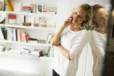 Portrait of businesswoman standing against wall  and talking on mobile phone