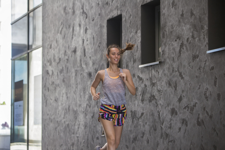 Young woman running on the street in urban environment