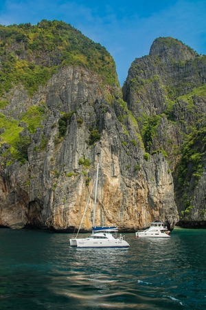 PHI PHI, THAILAND - DECEMBER 28, 2011: Boats at Maya Bay at Phi Phi archipelago in Thailand. Maya Bay has become the main tourist attraction of Phi Phi since The Beach was filmed here in 1999.
