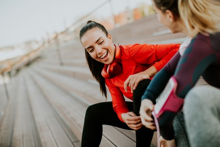 Two young attractive female runner taking break after jogging outdoors