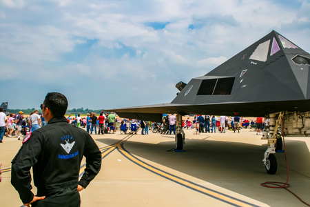 BARKSDALE, USA - APRIL 22, 2017: Unidentified man by Lockheed F-117 Nighthawk at Barksdale Air Base. Since 1933, the base has been inviting the public to view aircrafts at the annual airshow.