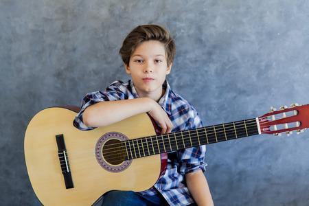 Cute teen boy with acoustic guitar Foto de archivo