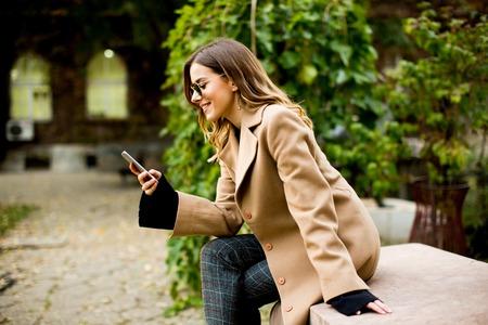 Zijaanzicht bij jonge vrouw buiten zitten en het gebruik van mobiele telefoon
