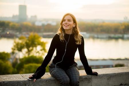 석양 야외 스마트 폰에서 유행 젊은 여자 듣는 음악의 초상화 스톡 콘텐츠 - 90951254