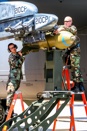 BARKSDALE, USA - APRIL 22, 2007: Boeing RC-135 Unindentified personel loading bombs on B-52 bomber at Barksdale Air Base. Since 1933, the base has been inviting the public to view aircrafts at the annual airshow.