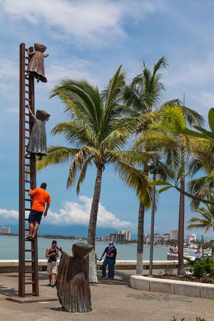 PUERTO VALLARTA, MEXICO - SEPTEMBER 6, 2015: Unidentified people by Searching for Reason statue at Puerto Vallarta, Mexico. Sculpure was made by Sergio Bustamante in 2000. Stock Photo - 89502835