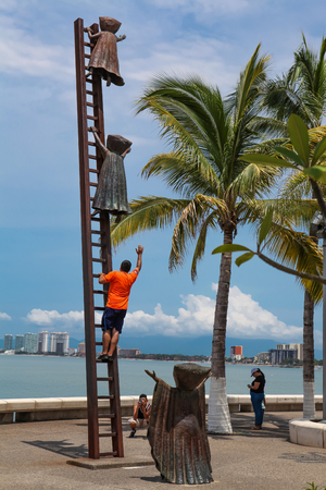 PUERTO VALLARTA, MEXICO - SEPTEMBER 6, 2015: Unidentified people by Searching for Reason statue at Puerto Vallarta, Mexico. Sculpure was made by Sergio Bustamante in 2000.