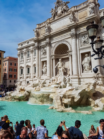 ROME, ITALY - SEPTEMBER 23, 2016: Unidentified people by Trevi Fountain in Rome, Italy. Trevi Fountain is designed by Italian architect Nicola Salvi and completed by Pietro Bracci at 1762.