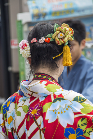 KYOTO, JAPAN - OCTOBER 7, 2016: Unidentified woman in traditional clothes near Fushimi Inari shrine in Kyoto, Japan. This popular shrine have 32,000 sub-shrines  throughout Japan