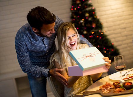 Happy young couple with present at Christmas time