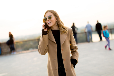 portrait de jeune femme avec des lunettes avec téléphone mobile en plein air