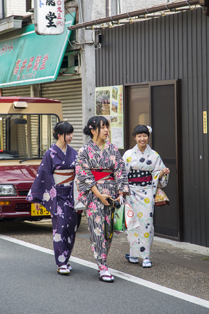 KYOTO, JAPAN - OCTOBER 7, 2016: Unidentified women in traditional clothes near Fushimi Inari shrine in Kyoto, Japan. This popular shrine have 32,000 sub-shrines  throughout Japan