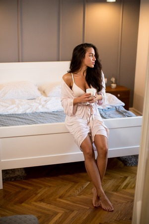 Portrait of young woman with mug in bedroom Stock Photo