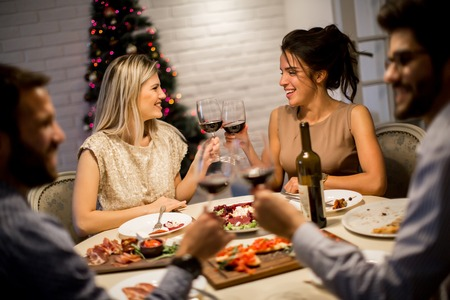 Friends celebrating Christmas or New Year eve at home Archivio Fotografico