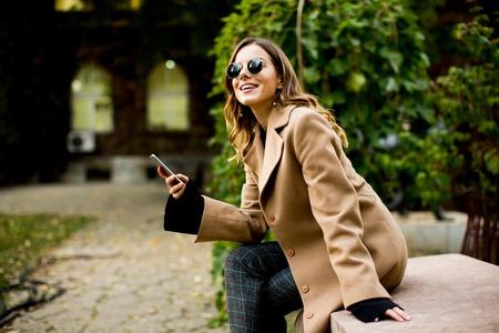 Bekijk moderne vrouw met behulp van mobiele telefoon in de herfst buiten