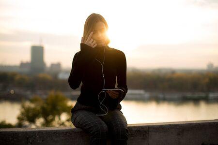 석양 야외 스마트 폰에서 유행 젊은 여자 듣는 음악의 초상화