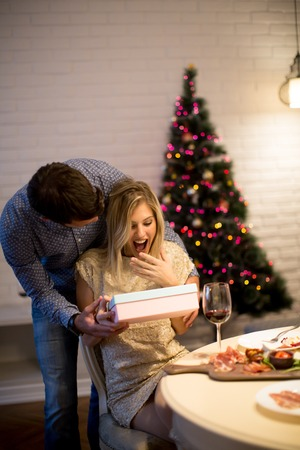 Happy young couple with present at Christmas time 版權商用圖片 - 90497562