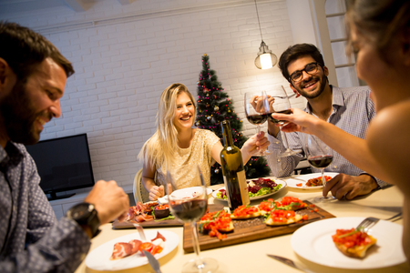 Group of young people celebrating New Year and drinking red wine Archivio Fotografico