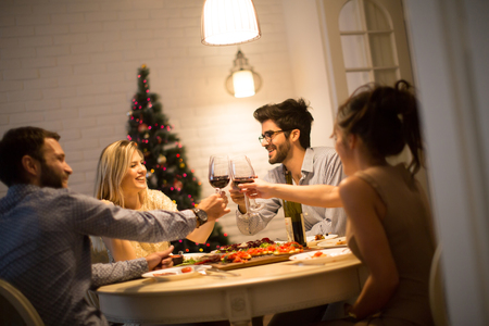 Friends celebrating Christmas or New Year eve at home Stock Photo