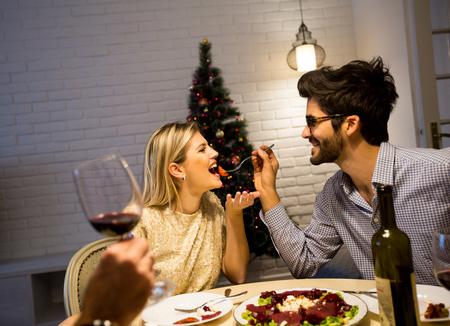 カップルはクリスマスツリーと美しく装飾された新年のインテリアでクリスマスディナーを持っています