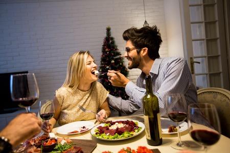 カップルのクリスマス ツリーで美しく装飾された新年インテリアでクリスマス ディナーがあります。