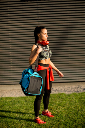 Young woman standing with sport bag outdoor