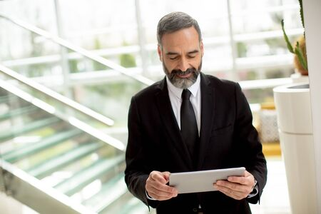 Handsome elegant serious Caucasian businessman with tablet in office Imagens