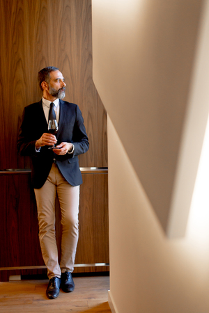Handsome elegant businessman drinking red wine in bar