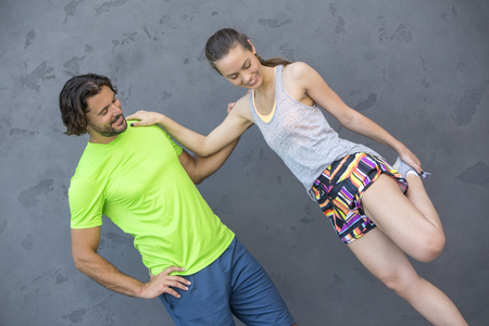 Young attractive woman exercising with a personal trainer outside at sunny day in urban enviroment